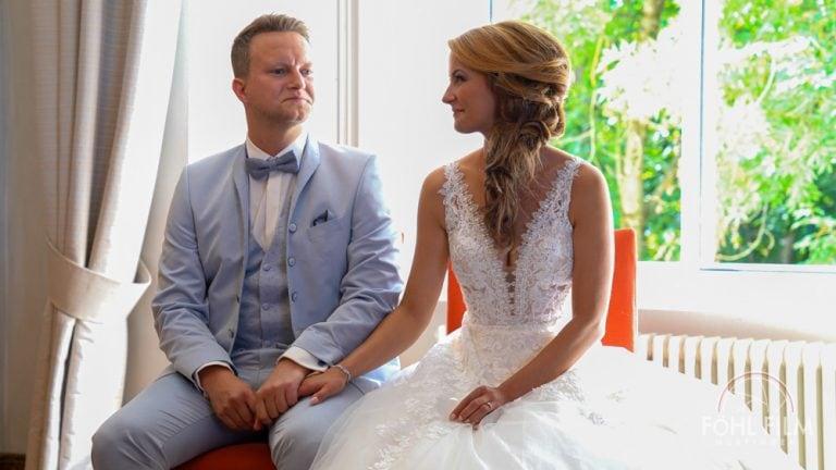 Brautpaar mit grauem Anzug und weißem Spitzenkleid sitzen im Trauzimmer